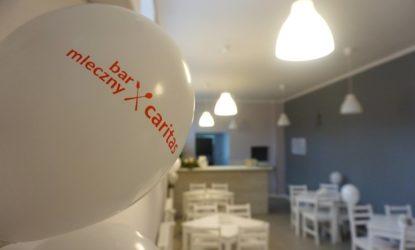 Zdjęcia ukazuje wnętrze lokalu gastronomicznego (stoliki z krzesłami, lada barowa), wnętrze jest utrzymane w jasnych kolorach. Na pierwszym planie widoczny jest biały balon, a na nim napis: bar mleczny caritas.