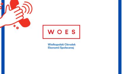 Grafika na białym tle, z niebieskim obramowaniem. Po lewej stronie widoczna czerwona słuchawka telefonu oraz dłoń, która trzyma tą słuchawkę. Na środku logo z napisem WOES (kolor czerwony), a poniżej Wielkopolski Ośrodek Ekonomii Społecznej (kolor niebieski).