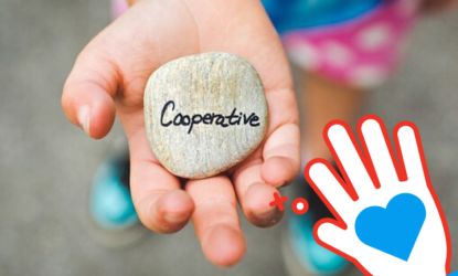 Zdjęcie przedstawia osobę, trzymającą w dłoni kamień. Kadr został wyostrzony na dłoń z kamieniem, na którym znajduje się napis w języku angielskim: Cooperative. Dodatkowo na zdjęciu dodano ikonę z dłonią, na której znajduje się serce.