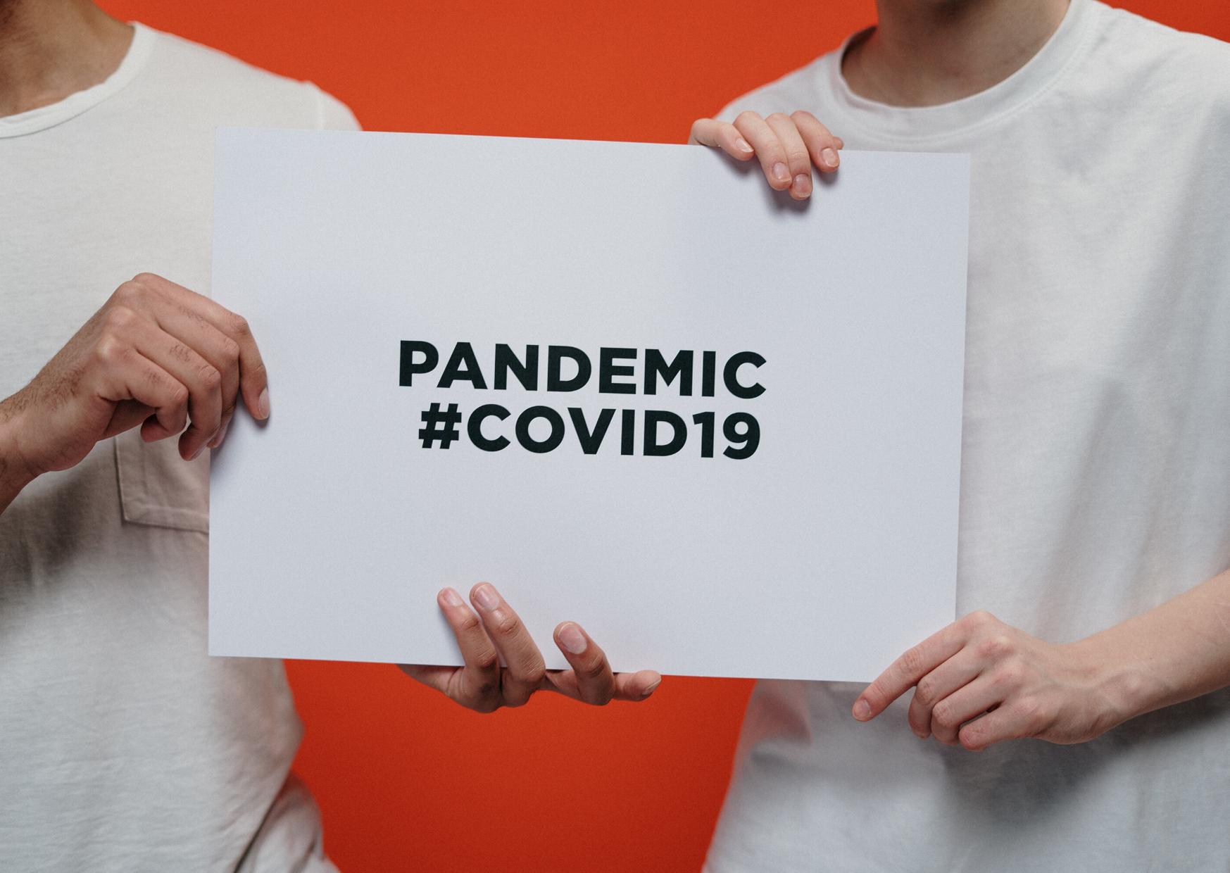 Grafika przedstawia dwie osoby, trzymające białą kartkę papieru. Na kartce jest nadrukowany napis: #COVID 19