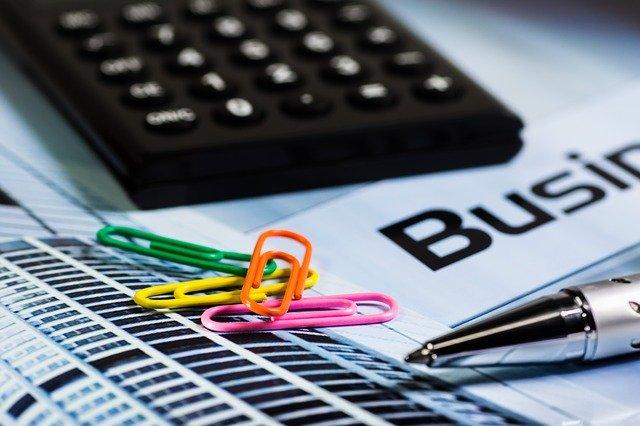 Na zdjęciu widoczne jest fragment blatu biurka/stołu a nim znajdują się akcesoria biurowe jak kalkulator, spinacze do dokumentów, długopis oraz kartki i dokumenty.
