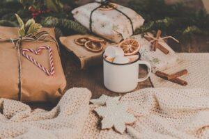 Zdjęcia przedstawia świąteczną (Boże Narodzenie) scenę. Prezenty, pierniki, kubek z ciepłym napojem, plastry pomarańczy, a wszystko na położone na kocu. W tle znajduje się choinka.