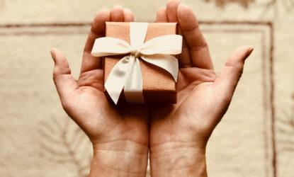 Zdjęcie przedstawia dłonie jednej osoby, wyciągnięte przed siebie. W dłoniach znajduje się prezent, mała zapakowana paczka z kokardą, np, na biżuterię.