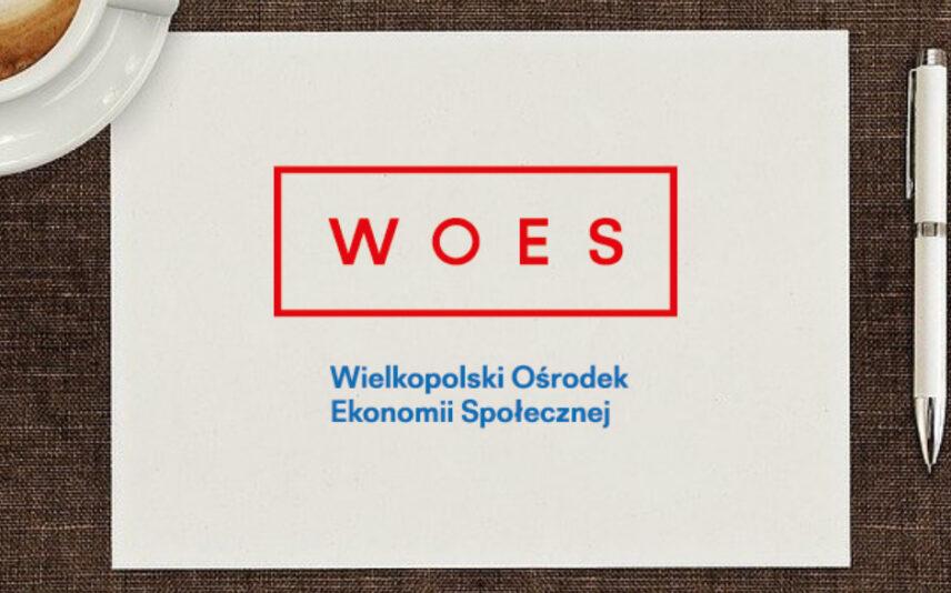 Widok z góry, całą powierzchnię zajmuje brązowe biurko a na nim na środku biała kartka, na niej logo WOES Wielkopolski Ośrodek Ekonomii Społecznej. Obok kartki leży długopis oraz filiżanka kawy.