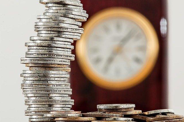 Zdjęcie, na pierwszym planie stos monet, w tle (zamglony) zegar ścienny