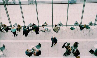 Zdjęcie przedstawia grupę osób skupionych wokół stolików, stojących, siedzących. Pomieszczenie w jakim się znajdują to prawdopodobnie sala konferencyjna. Zdjęcie wykonano z góry, z tzw. lotu ptaka.